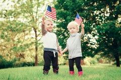 Behandla som ett barn barn med amerikanUSA-flaggor Arkivfoton