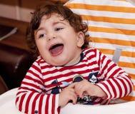 Behandla som ett barn barnet sitter i barns stol som att skratta jublar Royaltyfri Bild
