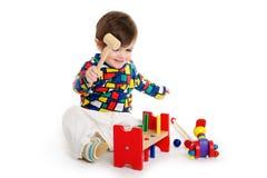 Behandla som ett barn barnet som spelar med leksaker Royaltyfria Bilder