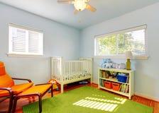 Behandla som ett barn barnkammarerumdesignen med den gröna filten, blåttväggar och den orange stolen. Arkivbild