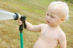 Behandla som ett barn bespruta den trädgårds- slangen Arkivfoton
