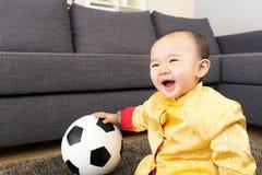 Behandla som ett barn bollen för pojkelekfotboll Arkivbild