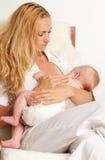 behandla som ett barn breastfeeding henne modern Royaltyfri Fotografi
