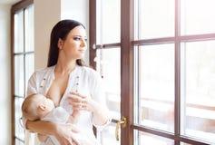 behandla som ett barn breastfeeding henne modern Fotografering för Bildbyråer
