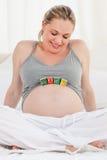 behandla som ett barn buken skära i tärningar henne gravid kvinna Arkivfoton