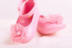 Behandla som ett barn bytar skor med rosetten för nyfödd flicka Arkivbilder
