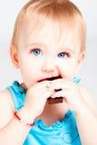 behandla som ett barn choklad äter flickan Arkivfoton