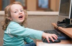 behandla som ett barn datorskrivbordsflickan little som ler genom att använda Arkivfoton