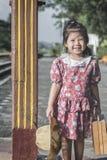 Behandla som ett barn den asiatiska flickan, medan vänta på drevet Arkivfoto