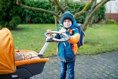 Behandla som ett barn den driftiga sittvagnen för den stolta pojken för den lilla ungen med nyfött Royaltyfri Foto