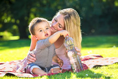 Behandla som ett barn den gripande vattenflaskan för pojken från moder Royaltyfria Bilder