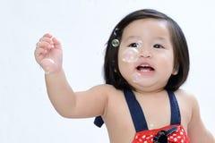 Behandla som ett barn den gulliga asiatet för closeupen flickan som spelar och skrattar till bubblor på Fotografering för Bildbyråer