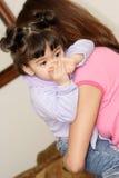 behandla som ett barn den gulliga flickaholdingen för babysitteren Royaltyfri Foto