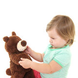 behandla som ett barn den gulliga flickan för björnen henne nallen Arkivfoton