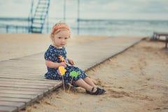 Behandla som ett barn den gulliga flickan med äpplekinden för blont hår som och rosa färgtycker om ferie för sommartid som mycket Arkivbild