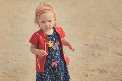 Behandla som ett barn den gulliga flickan med äpplekinden för blont hår som och rosa färgtycker om ferie för sommartid som mycket Arkivfoto