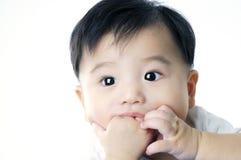 behandla som ett barn den gulliga handen hans begynna suga Royaltyfri Bild