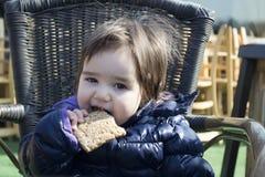 behandla som ett barn den gulliga kakan äter flickan Royaltyfri Bild