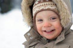 behandla som ett barn den gulliga skratta snowvintern för pojken Arkivbild