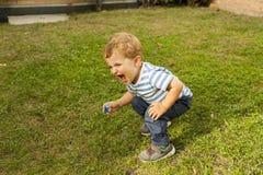 Behandla som ett barn den gulliga smileyen för full skottstående pojken som är satt i gräset Royaltyfri Fotografi
