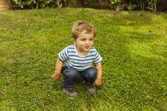 Behandla som ett barn den gulliga smileyen för full skottstående pojken som är satt i gräset Royaltyfri Foto