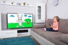 Behandla som ett barn den hållande ögonen på tecknade filmen för flickan på television arkivbild