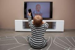 Behandla som ett barn den hållande ögonen på televisionen för pojken Fotografering för Bildbyråer