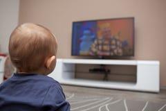 Behandla som ett barn den hållande ögonen på televisionen för pojken Royaltyfria Foton