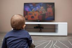 Behandla som ett barn den hållande ögonen på televisionen för pojken Royaltyfri Fotografi