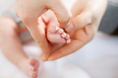 Behandla som ett barn den hållande foten för fadern eller för modern av nyfött Royaltyfri Fotografi