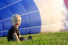 Behandla som ett barn den hållande ögonen på ballongen för varm luft för att fylla Royaltyfri Foto