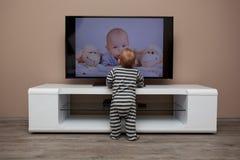 Behandla som ett barn den hållande ögonen på televisionen för pojken Royaltyfria Bilder