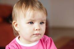 Behandla som ett barn den hållande ögonen på tv:n för flickan Arkivfoton