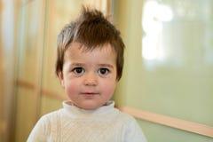 Behandla som ett barn den inomhus ståenden för closeupen av pojken med styggt hår De olika sinnesrörelserna av ett barn arkivbilder