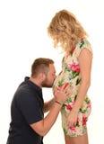 Behandla som ett barn den kyssande gravida kvinnan för mannen bulan Arkivfoton