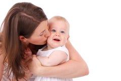 behandla som ett barn den kyssande modern Royaltyfria Bilder
