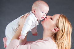 behandla som ett barn den kyssande modern för pojken Fotografering för Bildbyråer