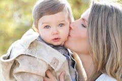 behandla som ett barn den kyssande modersonen för familjen Arkivfoton
