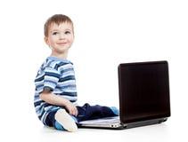 Behandla som ett barn den leka bärbar dator för pojken arkivfoton