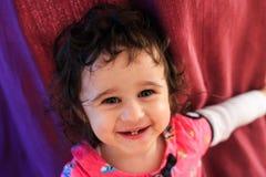 Behandla som ett barn den lockiga flickan som ler på en röd bakgrund royaltyfria foton