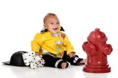 behandla som ett barn den lyckliga brandmannen Royaltyfri Bild