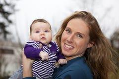 behandla som ett barn den lyckliga holdingmodern för flickan Arkivfoto