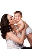 behandla som ett barn den lyckliga kyssande modern för kinden Fotografering för Bildbyråer