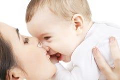 behandla som ett barn den lyckliga kyssande modern för pojken Arkivfoton