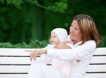 behandla som ett barn den lyckliga modern för bänken Royaltyfri Bild