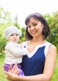 Behandla som ett barn den lyckliga modern för det blandade loppet med ståenden för flickan utomhus Royaltyfri Fotografi