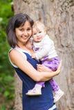 Behandla som ett barn den lyckliga modern för det blandade loppet med ståenden för flickan utomhus Arkivfoton