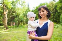 Behandla som ett barn den lyckliga modern för det blandade loppet med ståenden för flickan utomhus Arkivbild