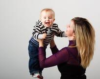 behandla som ett barn den lyckliga modern för pojken Arkivbilder