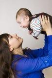 behandla som ett barn den lyckliga modern för pojken Royaltyfri Foto